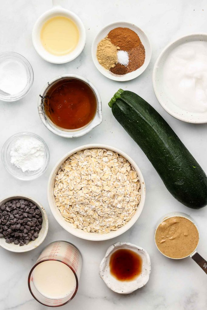 oatmeal zucchini muffin ingredients in white bowls on a blue backdrop