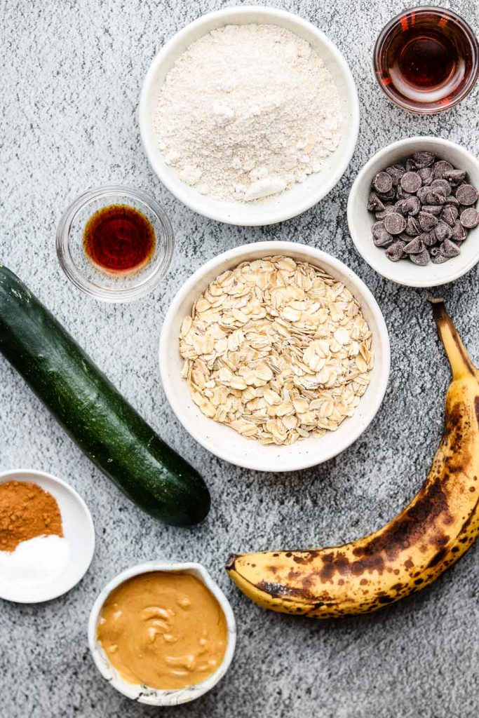 ingredients for healthy vegan zucchini oatmeal cookies in white bowls on a black backdrop