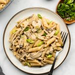 mushroom pasta on a white plate with scallions garnished on top