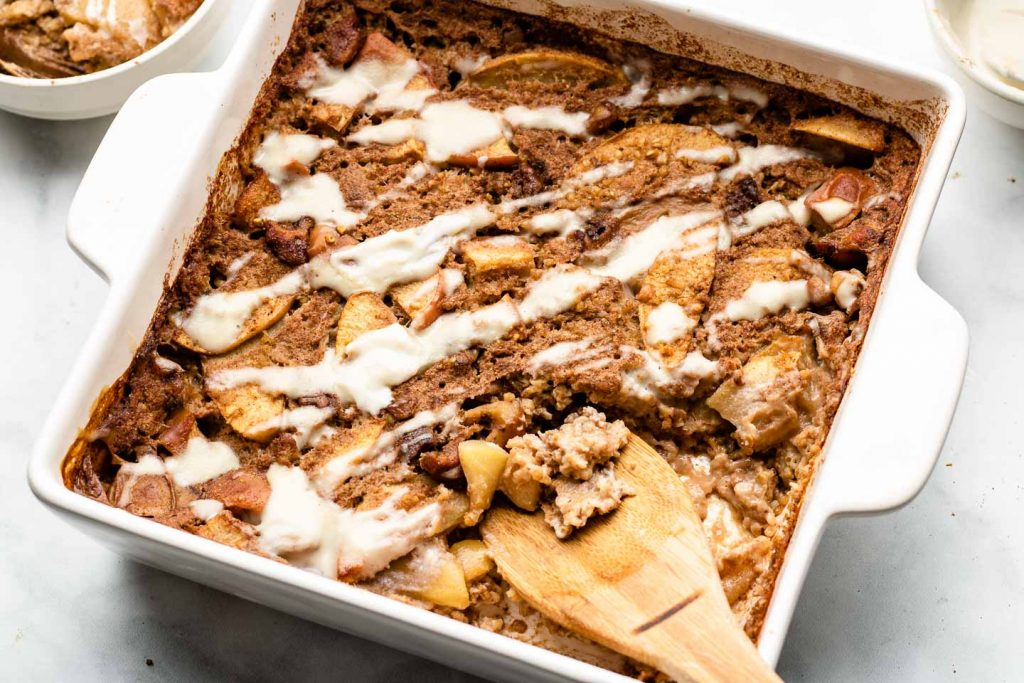 steel cut apple baked oatmeal in a 8x8 inch white baking dish with cashew maple cream drizzled on top