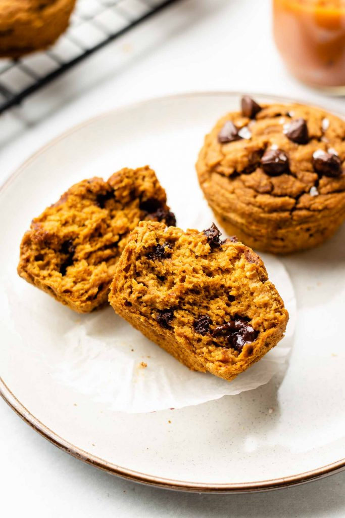 healthy pumpkin chocolate chip muffins on a white plate sliced in half
