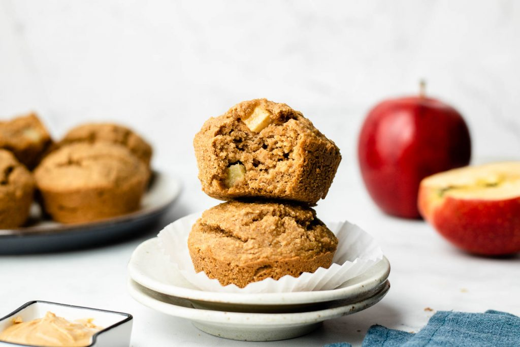 healthy oat apple muffins stacked on a speckled small plate with a bite taken out of the top muffins and apples in the background
