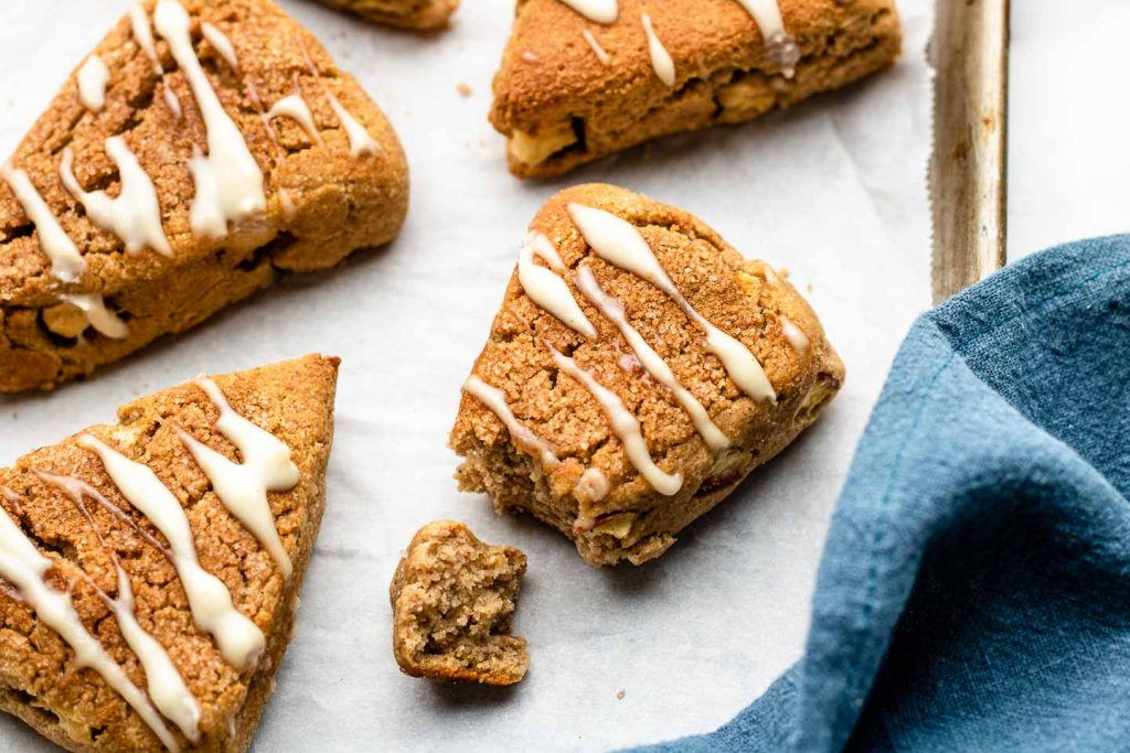 apple cinnamon scones with maple glaze on top on a baking sheet with a blue cloth in the corner