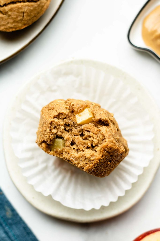 healthy apple cinnamon oatmeal muffin on a small white plate with a bite taken out of it
