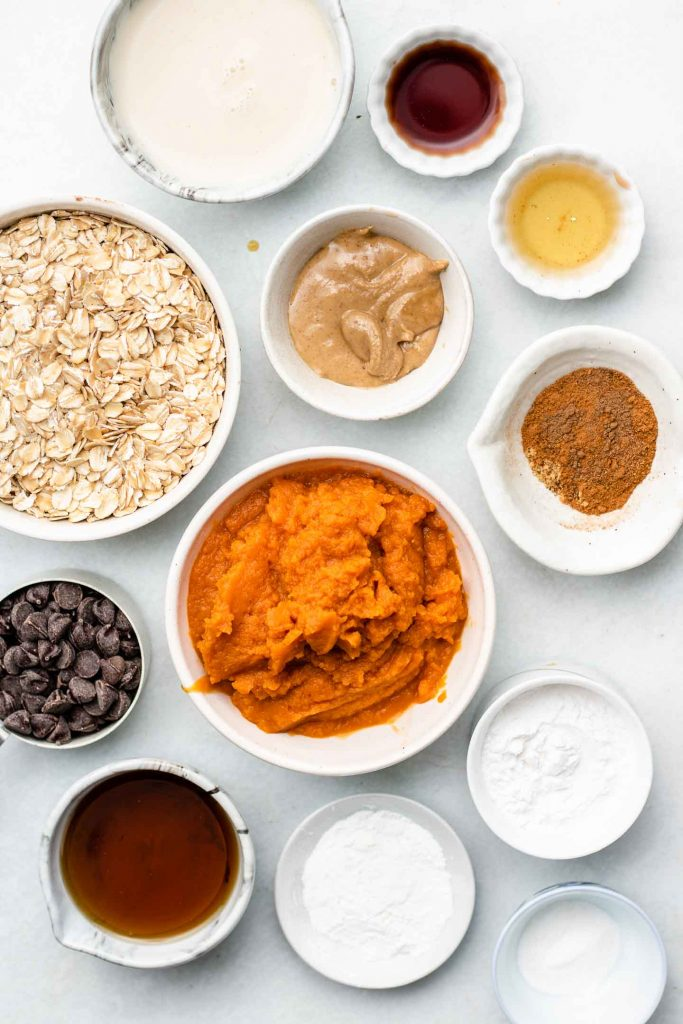 ingredients for flourless vegan pumpkin muffins in small bowls on a blue backdrop