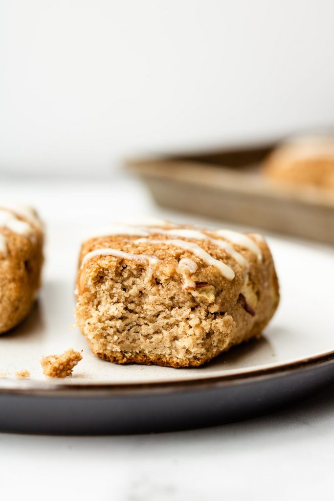 apple cinnamon sugar scones with a bite taken out of it on a white and blue ceramic plate