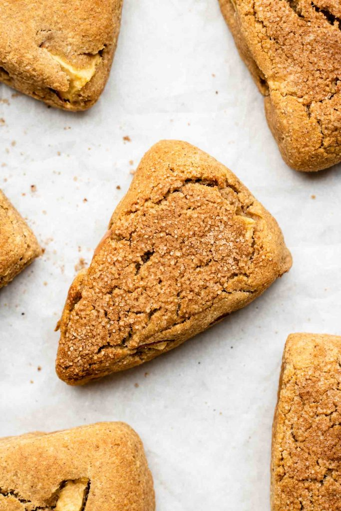 apples scones coated in cinnamon sugar on parchment paper