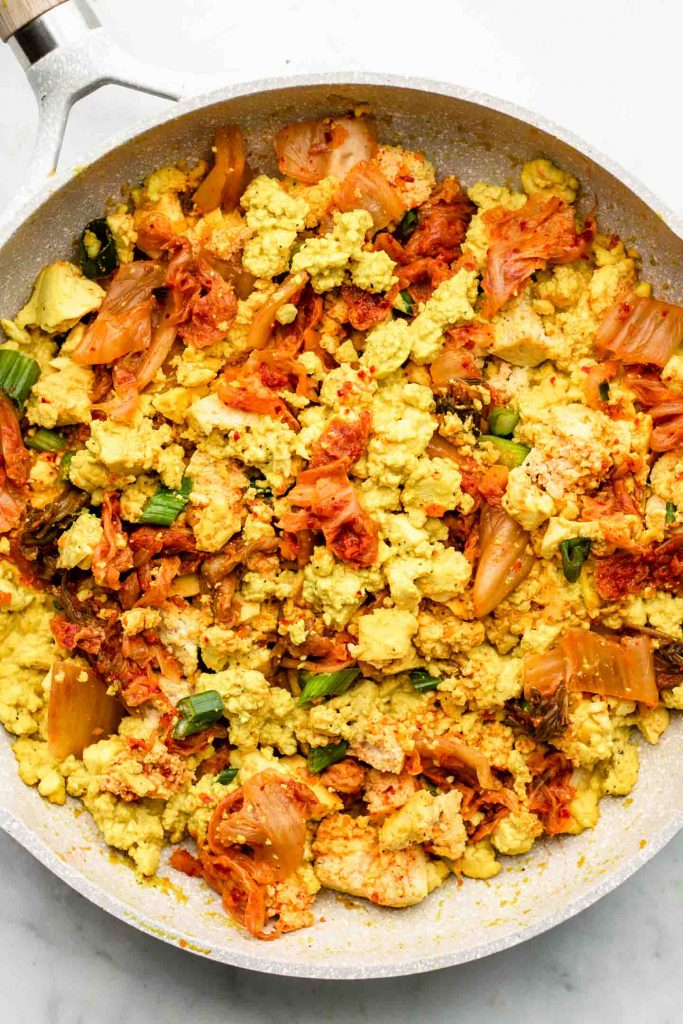 scrambled tofu with kimchi in a white speckled pink pan