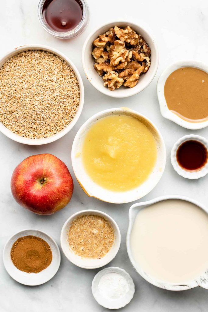 ingredients for apple baked oatmeal in bowls on a marble backdrop