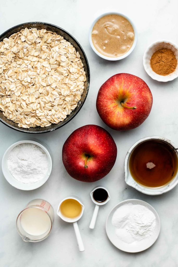 ingredients for healthy apple cinnamon muffins in bowls on a blue backdrop