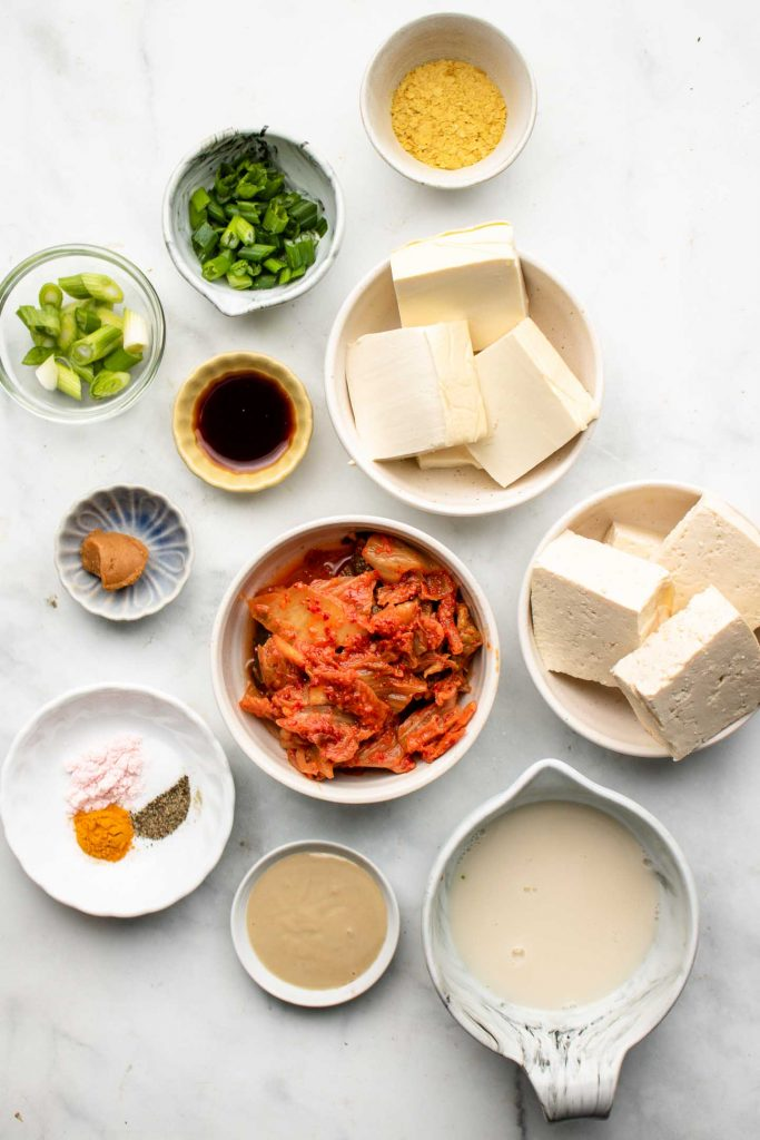 ingredients for kimchi tofu scramble in bowls on a marble backdrop