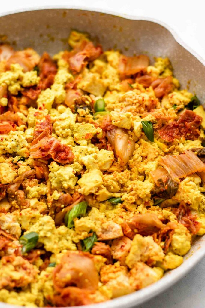 close of shot of tofu scramble in a speckled pink pan with kimchi and scallions