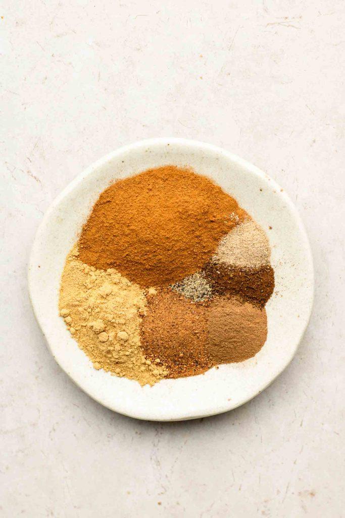 cinnamon, ginger, nutmeg, all spice, cloves, cardamom and black pepper on a speckled white plate