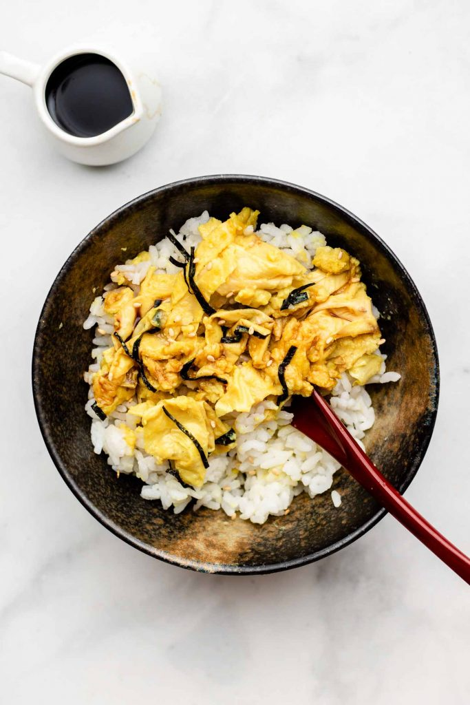 japanese scrambled eggs over a bed of rice in a bowl topped with nori and a spoon inside the bowl