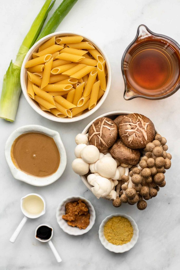 ingredients for creamy miso mushroom pasta in white bowls on a marble backdrop