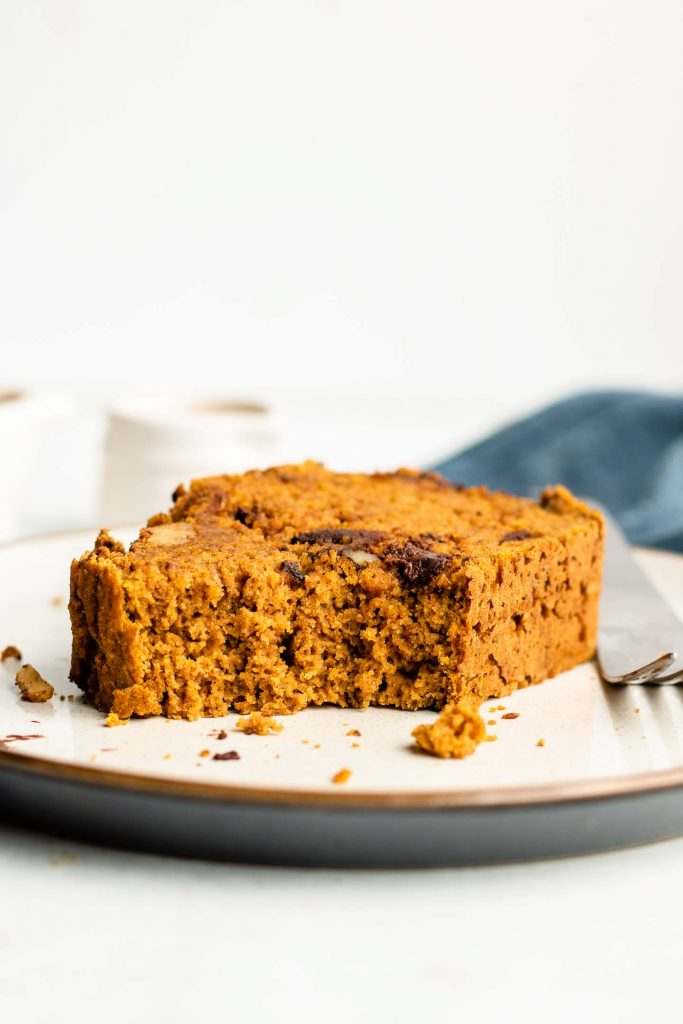bite shot of pumpkin bread on a white plate