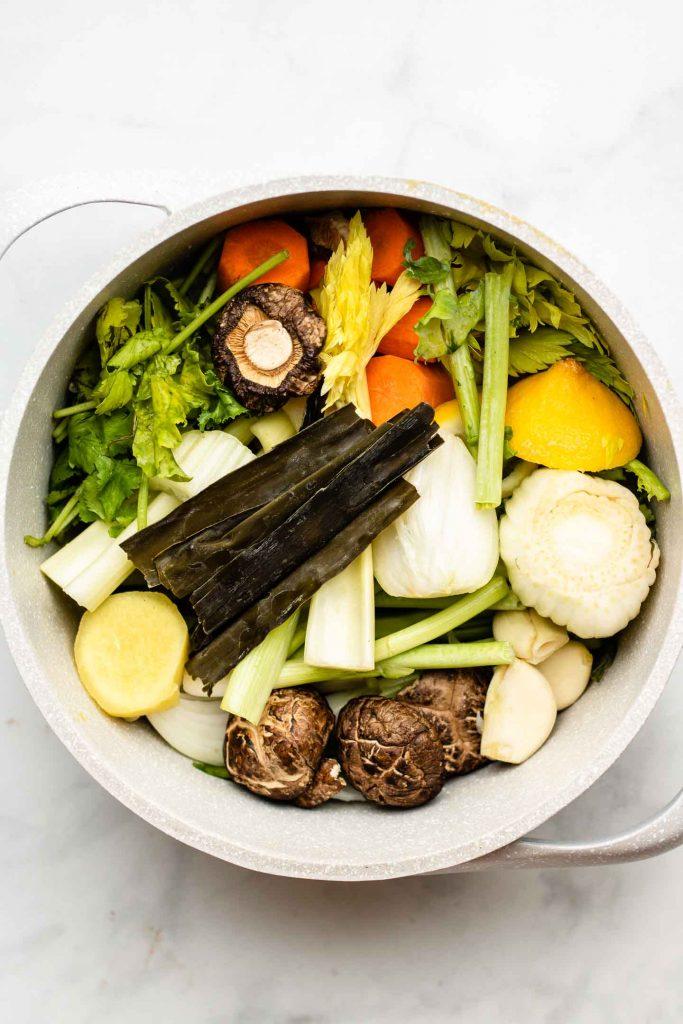 ingredients for vegan umami bone broth in a speckled pink pot
