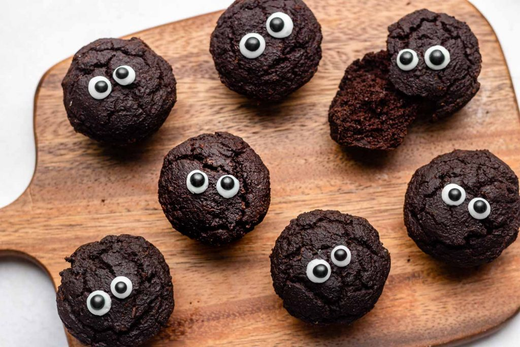 brownie bites with googly eyes on a wooden cutting board