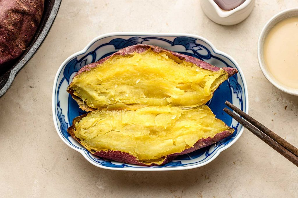 roasted japanese sweet potato sliced in half in a blue rectangle bowl