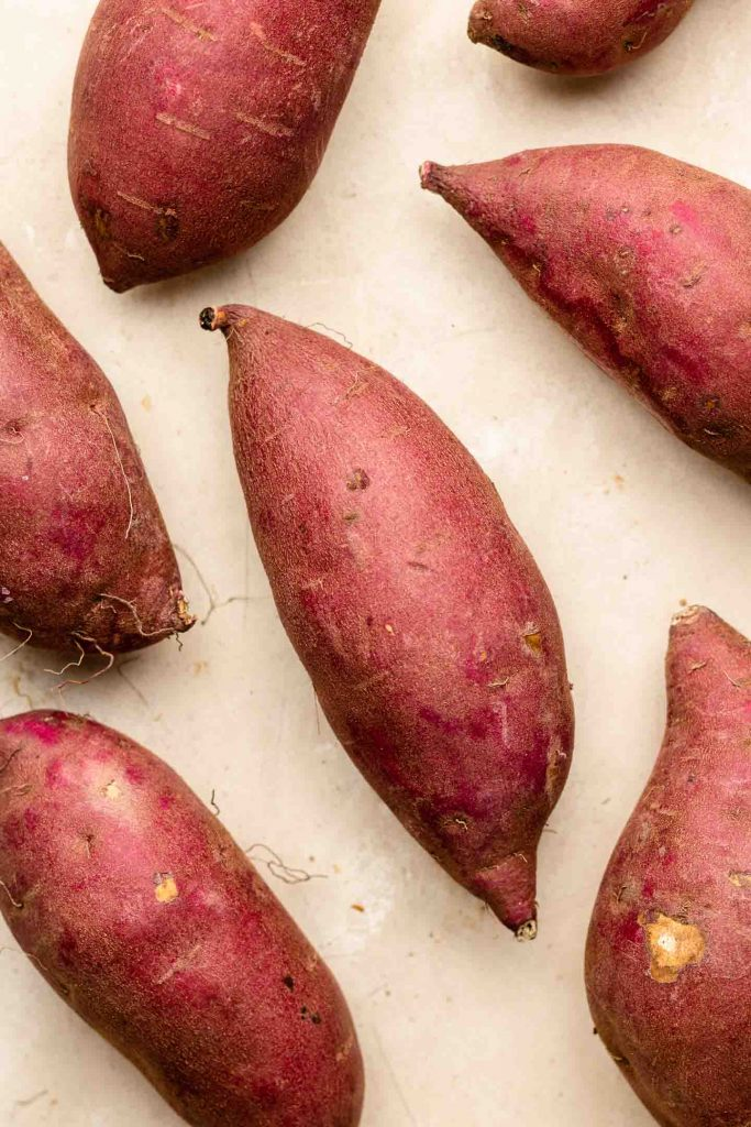 japanese sweet potatoes scattered on a beige backdrop