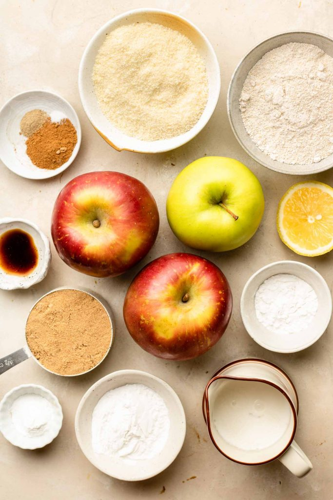 ingredients for apple cobbler in small bowls on a beige backdrop