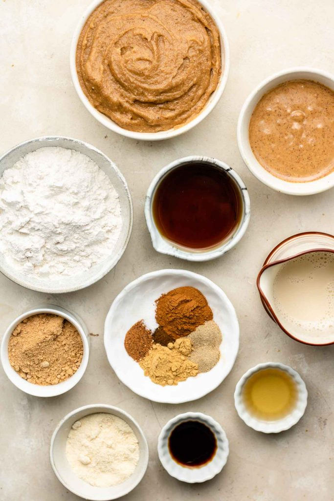 vegan chai spiced cupcake ingredients in white bowls on a beige backdrop