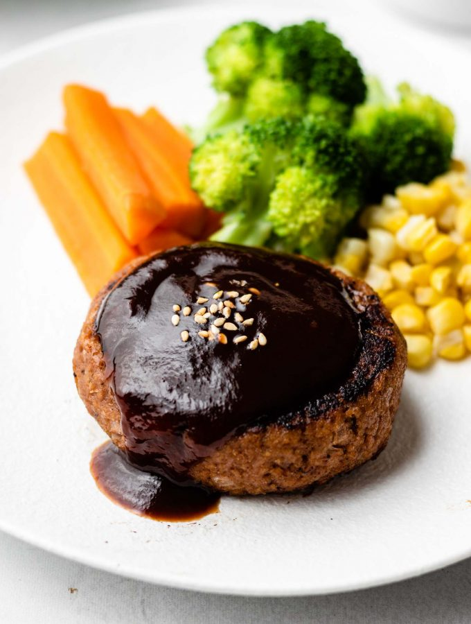 close up shot of hamburger steak with red wine reduction sauce over it