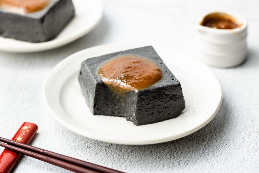 block of goma dofu on a white plate with miso sauce on top