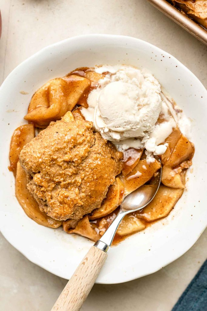 close up shot of apple cobbler in a bowl half eaten with ice cream