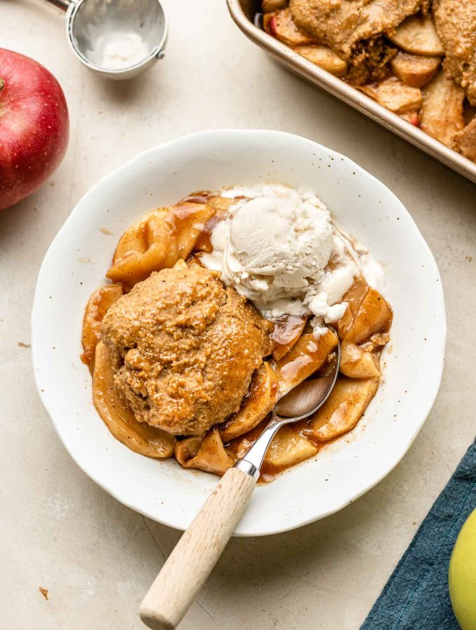 apple cobbler with biscuit topping in a white bowl with non dairy ice cream on the side