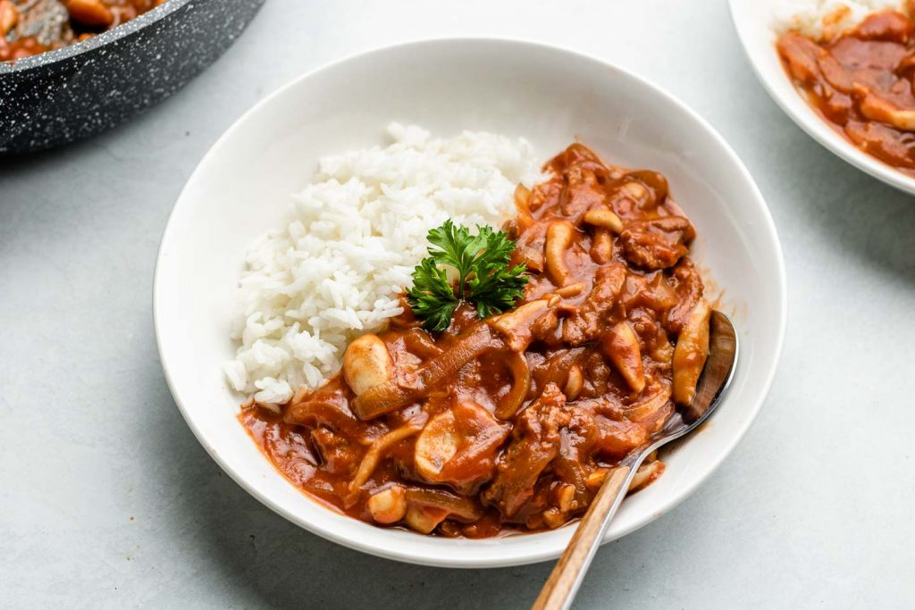 side shot of vegan tomato mushroom demiglace hayashi stew over rice in a white bowl and wooden spoon