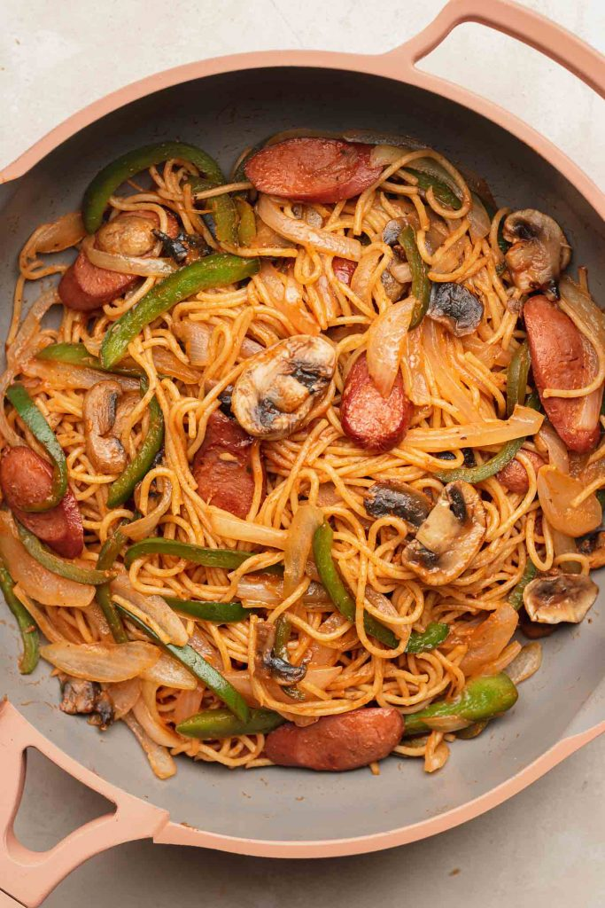 ketchup pasta with sausage, bell pepper and mushrooms in a pink fry pan