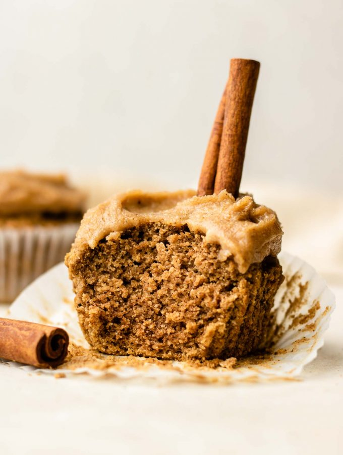 brown chai cupcake with chai frosting and a cinnamon stick on top, with a bite shot