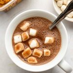 oat milk hot chocolate in a white mug with marshmallows