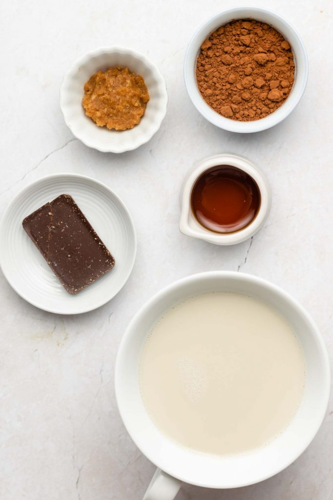 oat milk hot chocolate ingredients in white bowls