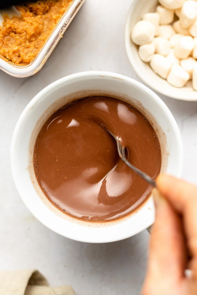 mixing a cup of hot chocolate with a spoon