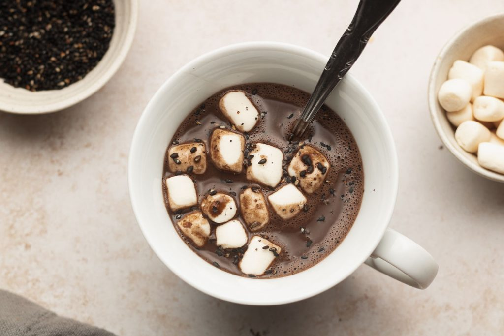 black sesame hot chocolate in a white mug with marshmallows on top