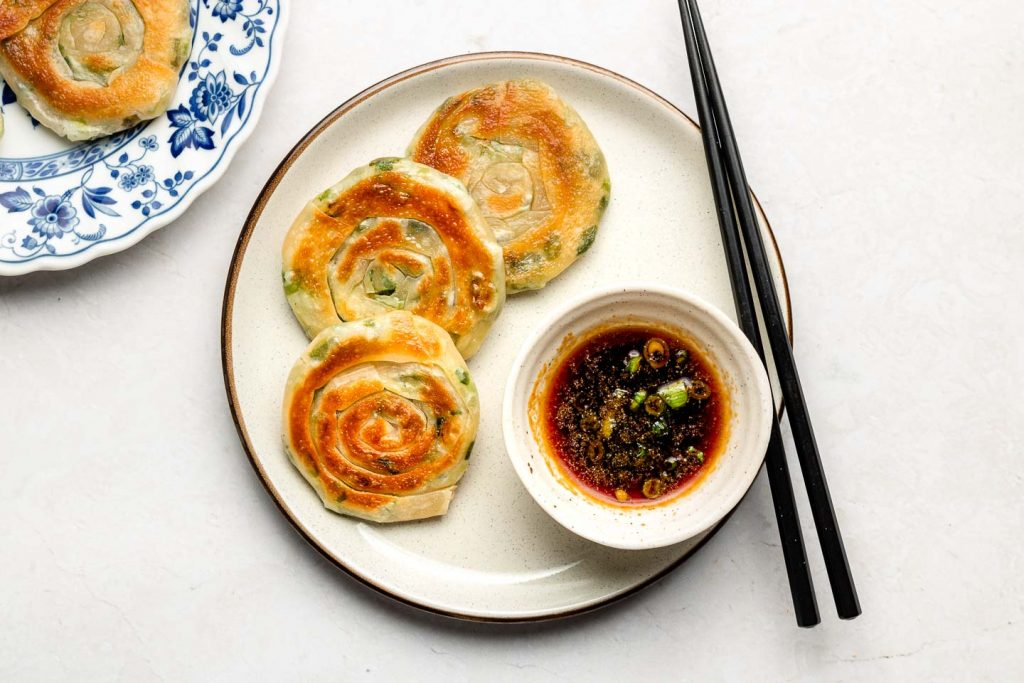 vegan scallion pancakes on a ceramic plate with soy ginger dipping sauce in a white bowl