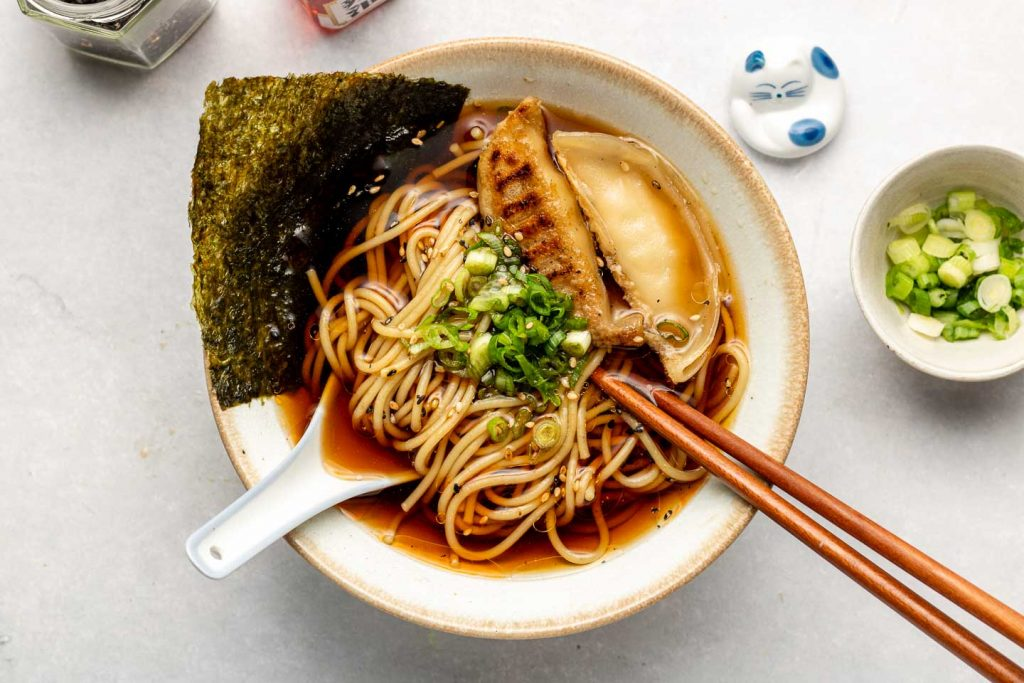 vegan shoyu ramen in a white bowl with gyoza dumplings, nori and scallions