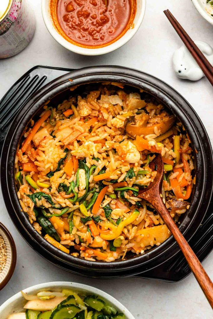 vegetarian bibimbap korean mixed rice bowl with gochuang sauce in a stone bowl