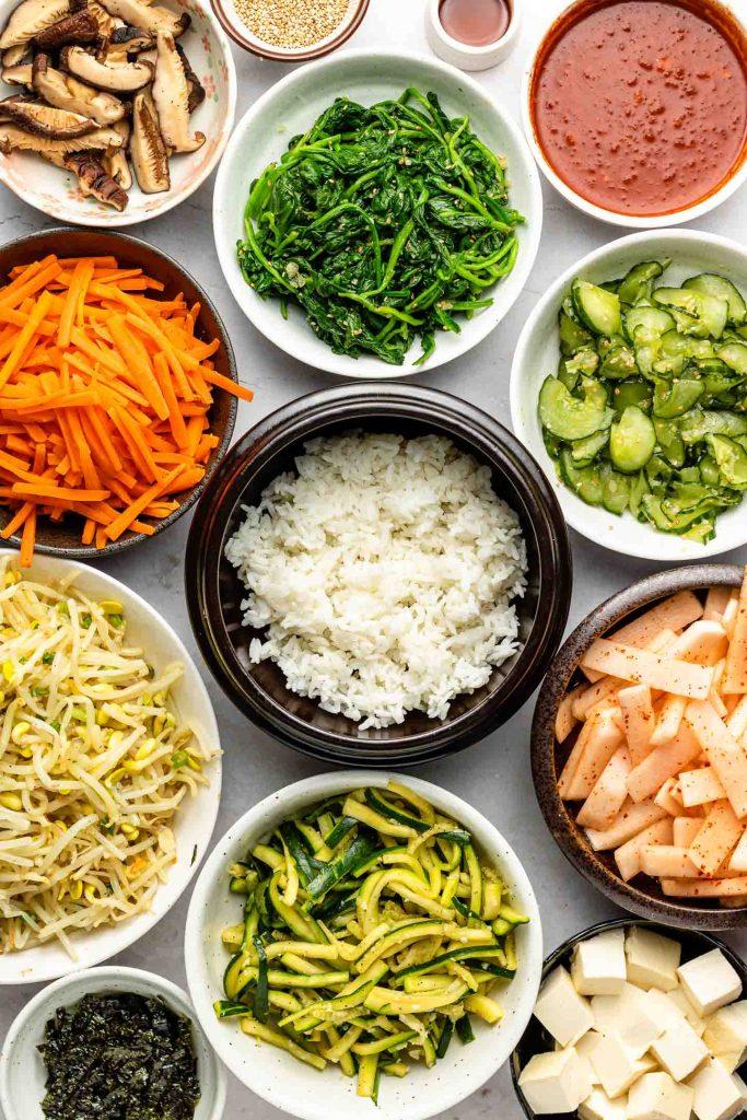 arrangement of korean side dishes for bibimbap in separate bowls
