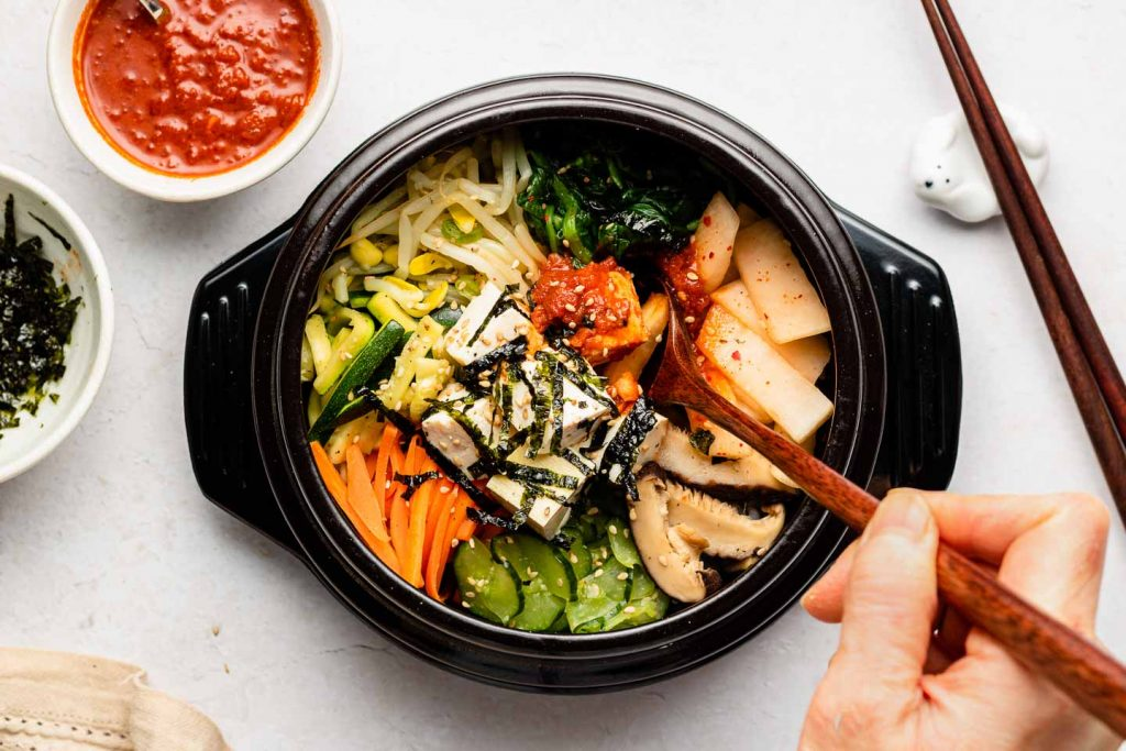 long wooden spoon scooping out of vegan bibimbap bowl in a stone bowl