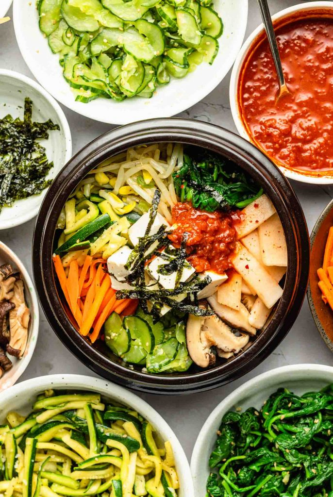 vegetarian bibimbap topped with colourful vegetables, tofu, seaweed and spicy sauce
