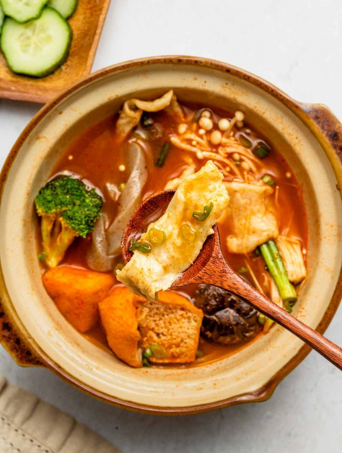 sichuan hot pot soup with fresh noodles in a clay pot wooden spoon holding a noodle