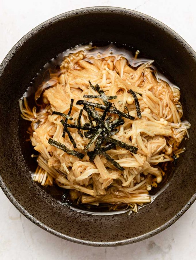 cooked enoki in a black bowl with soy butter sauce and nori on top