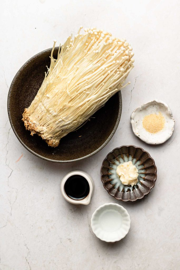 ingredients for japanese soy butter enoki mushrooms in bowls on a pearl back drop