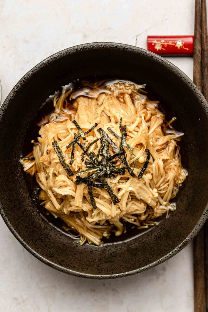 cooked enoki mushrooms in a black bowl with a soy butter sauce topped with nori strips