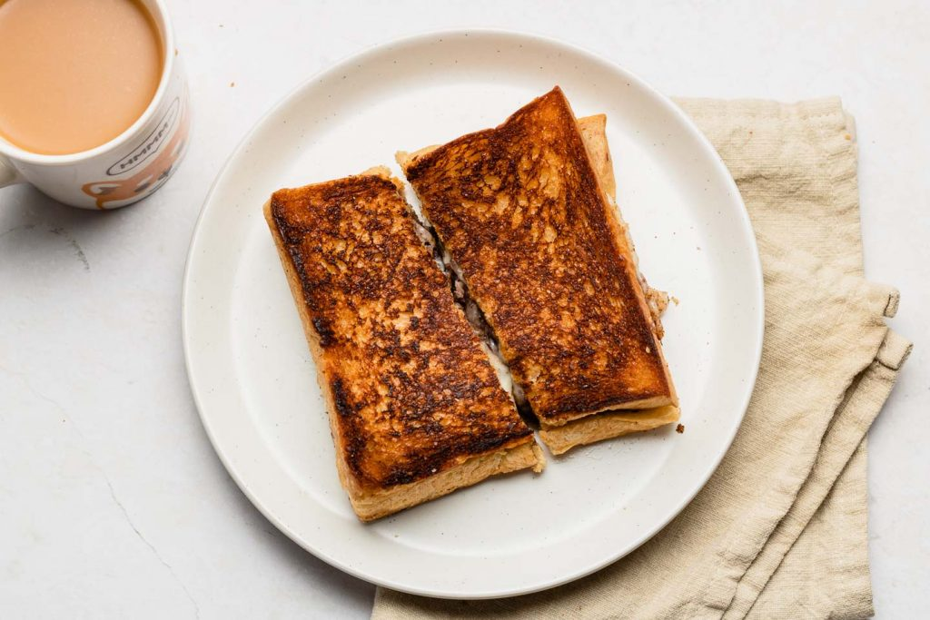 red bean paste grilled cheese on a white plate sliced in half