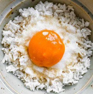 vegan egg yolk over rice in a ceramic green bowl