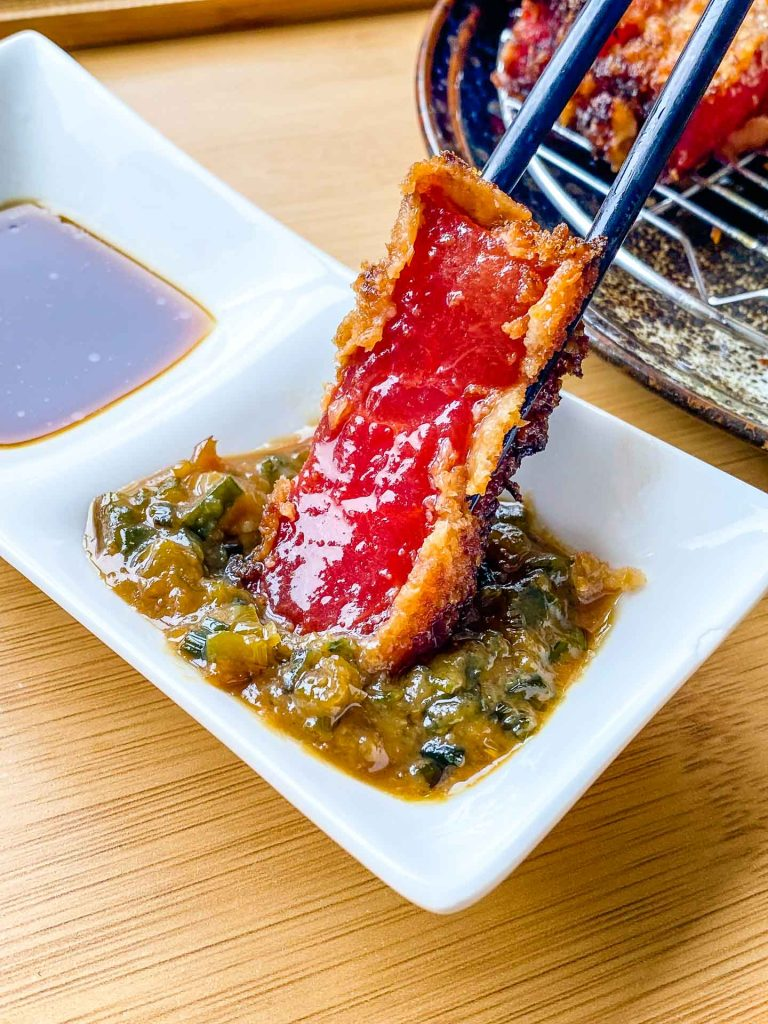 dipping gyukatsu in negi miso sauce
